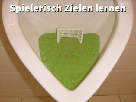 Urinal mit Fußball-Tor, der den Spieltrieb der Männer anspricht